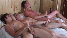 Three beautiful and horny young guys masturbating together on the bed