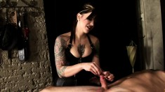 Tattooed dominatrix gives an ice bath to a slave's cock in bondage