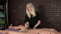 Tattooed stud in bondage gets his cock squeezed and stroked by a blonde mistress