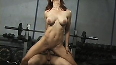 Big breasted redhead gets her holes fucked hard by two guys in the gym