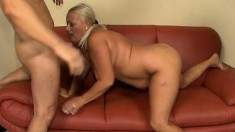 Busty mature blonde has a young stud pounding her holes on the couch